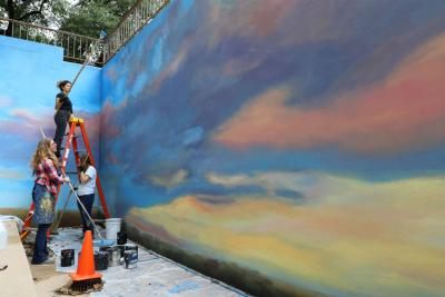 Three people paint a mural with sky and clouds on a concrete wall.