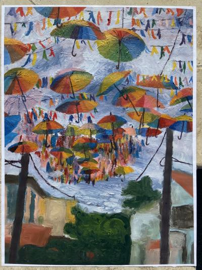 A painting of colorful umbrellas suspended above a street scene.