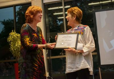 Christina Bain presents alumnaLiz Abrahams with an award.