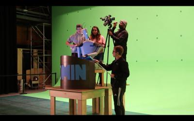 students work a robot puppet in front of a green screen