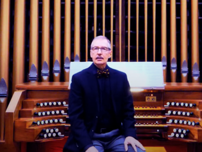 Lecturer Gregory Eaton in front of an organ