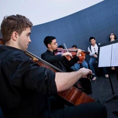 A cellist and violinist play to an audience in James Turrell's skyspace