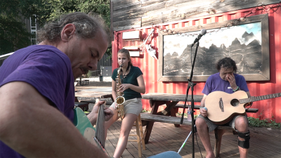 A person wearing a skirt plays a saxophone, flanked by a person playing an acoustic guitar and a bass.