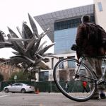 A man with a bicycle looks at a sculpture made of silver canoes.