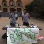 Students give a thumbs up sign at a table with baked goods on it.