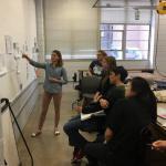 Caroline Rock points to a whiteboard