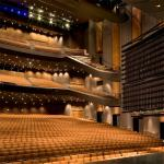 An image of Bass Concert Hall at the University of Texas at Austin. The hall has multiple levels with yellow seats and blue and white lights overhead.