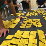 students surround a table filled with yellow post-it notes in the school of design and creative technologies