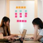 """Two women sit at a table working on laptops. There is a white board filled with pink and orange sticky notes that say """"Work In More You"""""""