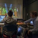 Kate Ducy and Sven Ortel work on projection design for President Fenves' inauguration. Photo by Michael Arbore.
