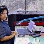 Yael Kanarek sits at a table covered in art supplies