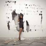 A woman breaks through a wall as part of an art exhibition