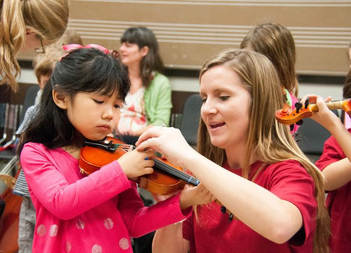 A teacher helps a young student with her violin.