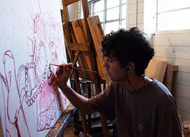 A student paints in the studio as part of the Studio Art minor program.