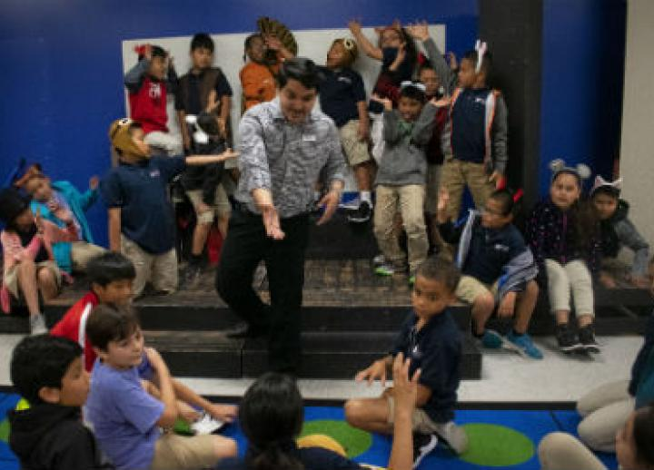 A UTeach Theatre student works with students in an elementary school class.