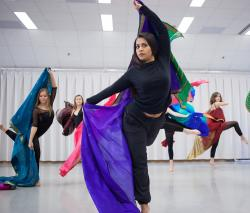 Sofia performs dance moves while holding an Indian sari