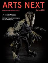 an image of the cover of Arts Next magazine, with a black background an actor wearing an animatronic raptor costume