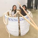 Two girls sit in a large bowl