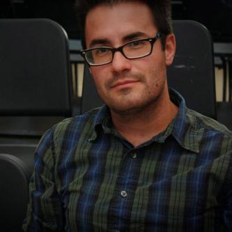 An image of CARE counselor Nathan Langfitt, who has dark hair, is wearing glasses and a blue and green checkered shirt