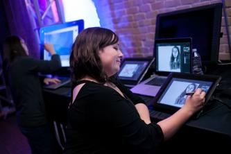 A student draws on a tablet as part of the launch event for the Center for Arts and Entertainment Technologies.