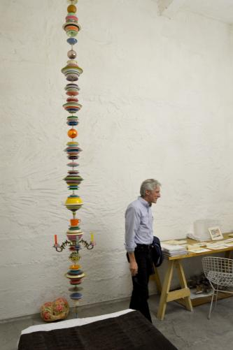 Dean Doug Dempster stands next to a Thomas Glassford piece that uses stacked melamine plates. Photo by Alicia Dietrich.