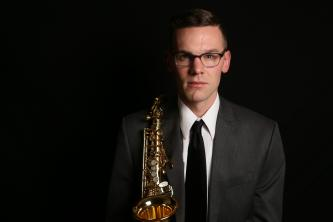 Nathan%20Mertens%20holds%20a%20saxophone