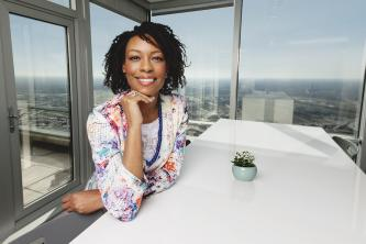 Sammetria Goodson sits at a white table with a view of downtown Dallas behind her.