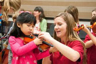 A Butler School of Music student works with a child as part of the String Project program.